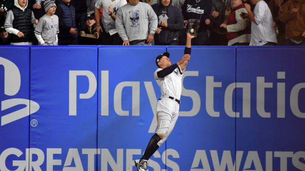 Oct 16, 2017; Bronx, NY, USA; New York Yankees right fielder Aaron Judge (99) makes a catch while jumping into the outfield wall during the fourth inning against the Houston Astros during game three of the 2017 ALCS playoff baseball series at Yankee Stadium. Mandatory Credit: Robert Deutsch-USA TODAY Sports